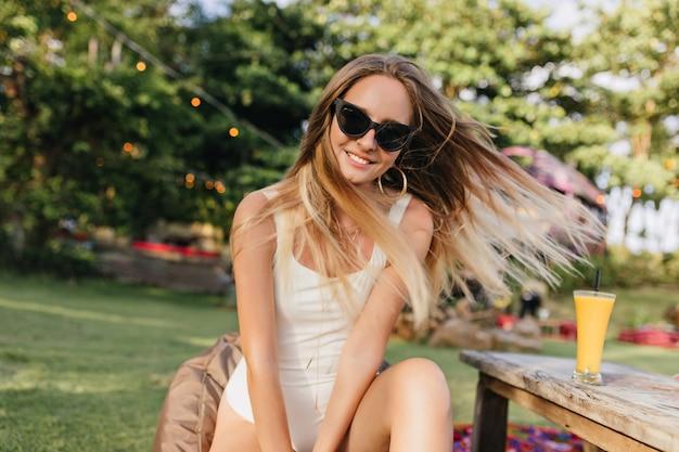 Schöne sorglose frau mit langen haaren, die auf natur aufwerfen und lächeln. romantisches gegerbtes weibliches modell, das im park mit glas kaltem orangensaft sitzt.