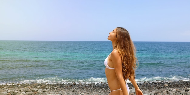 Schöne sorglose frau tiefen atem am strand