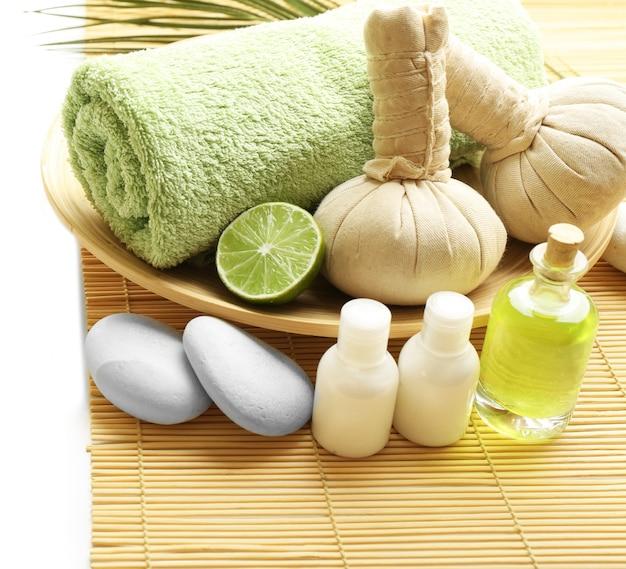 Schöne spa-komposition. kräuterkugeln und handtuch in der schüssel. kieselsteine und kosmetika hautnah