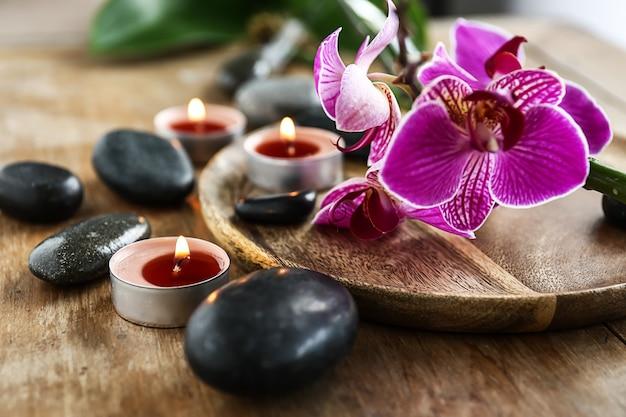 Schöne spa-komposition mit steinen, kerzen und blumen auf tisch, nahaufnahme