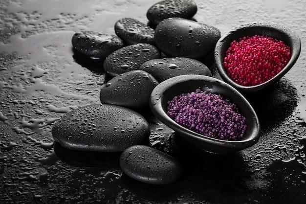 Schöne spa set spa produkte mit ätherischen ölen, seife, handtuch, spa sea salz auf dunklen nassen hintergrund. horizontal mit kopierraum.