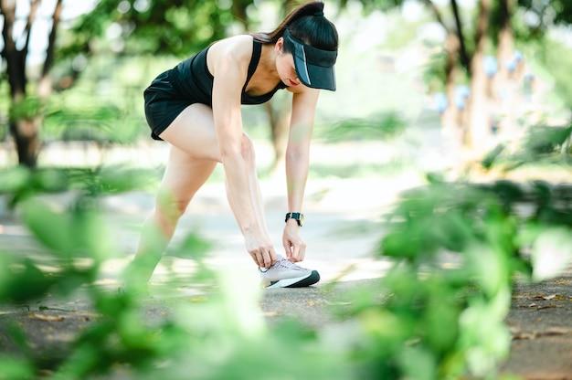 Schöne sport asiatische frau mittleren alters, die draußen an einem schönen sommertag ihre schnürsenkel bindet.