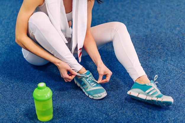 Schöne sportfrau mit perfektem körper, der schnürsenkel auf turnschuhen im fitnessstudio bindet