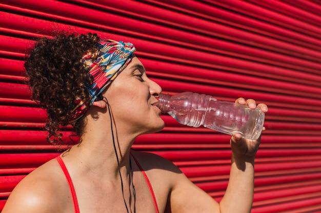 Schöne sportlerin, die wasser trinkt und musik mit kopfhörern hört