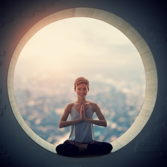 Schöne sportlich fit yogi frau praktiziert yoga asana padmasana - lotus pose in einem runden fenster