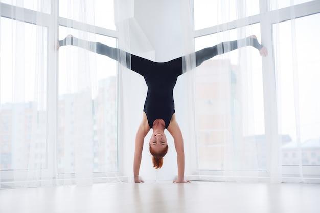 Schöne sportlich fit yogi frau praktiziert yoga handstand asana adho mukha vrikshasana im yoga studio.