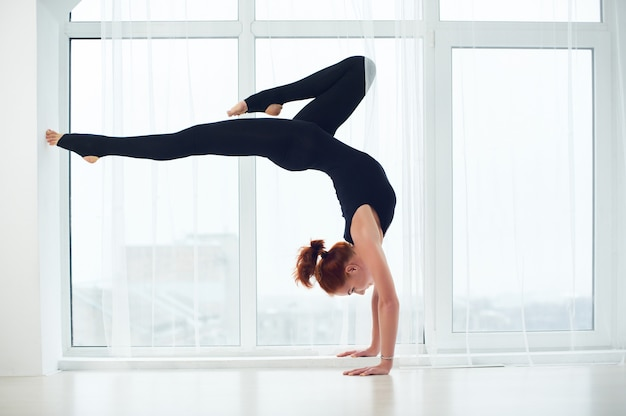Schöne sportlich fit yogi frau praktiziert yoga handstand asana bhuja vrischikasana
