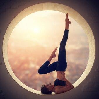 Schöne sportlich fit yogi frau praktiziert yoga salamba sarvangasana - schulterstand pose in einem fenster