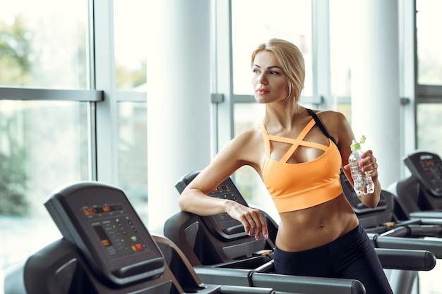 Schöne sportliche blonde frau mit einer flasche wasser auf einem laufband im fitnessstudio.