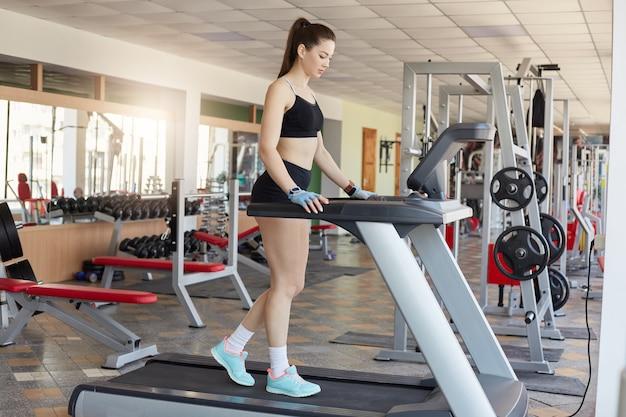 Schöne sportliche frau auf laufband. junge brünette schlanke fitnessfrau, die auf laufmaschine in der modernen turnhalle steht und sich auf training vorbereitet