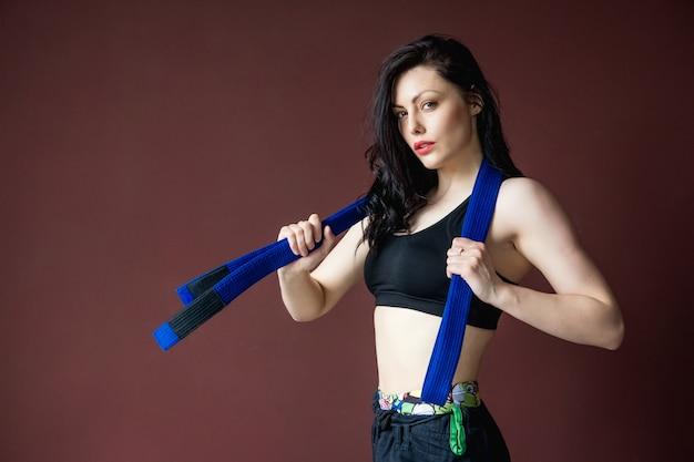 Schöne sportliche frau des porträts mit blauem gürtel auf dem wandhintergrund kampfkunstkonzept