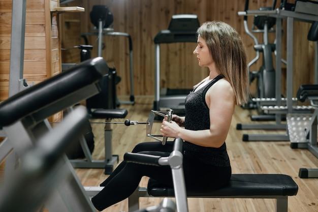Schöne sportliche frau, die gewicht im fitnessstudio auf trainingsgerät hebt. powerlifter mittleren alters mit tätowierung. starker und fitter körper, gesundes lifestyle-konzept. frau mit 40