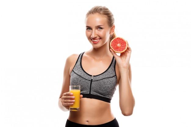 Schöne sportliche frau, die grapefruit und saft hält