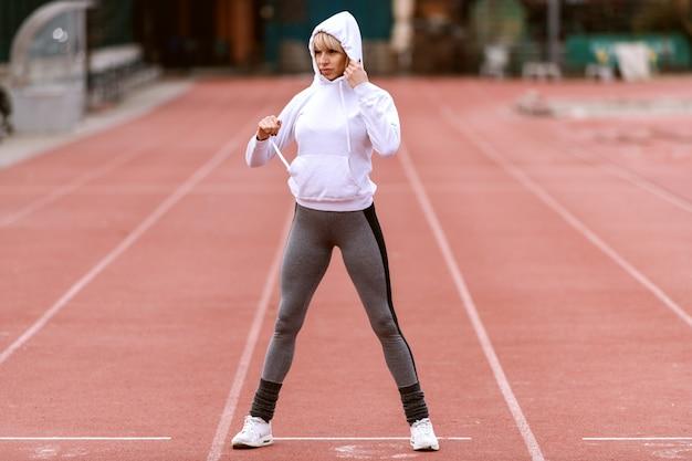 Schöne sportliche frau, die hoodie anzieht, während sie auf der rennstrecke steht.