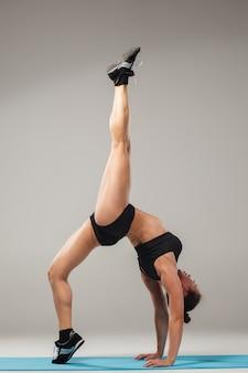 Schöne sportliche frau, die in der akrobatenhaltung steht
