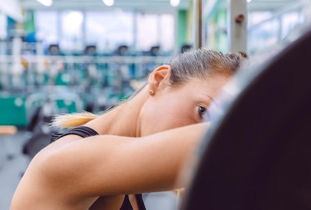 Schöne sportliche frau, die müde ruht, nachdem sie die langhantel auf einem muskeltraining im fitnesscenter gehoben hat