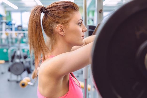 Schöne sportliche frau, die sich nach dem heben der langhantel auf einem muskeltraining im fitnesscenter ausruht