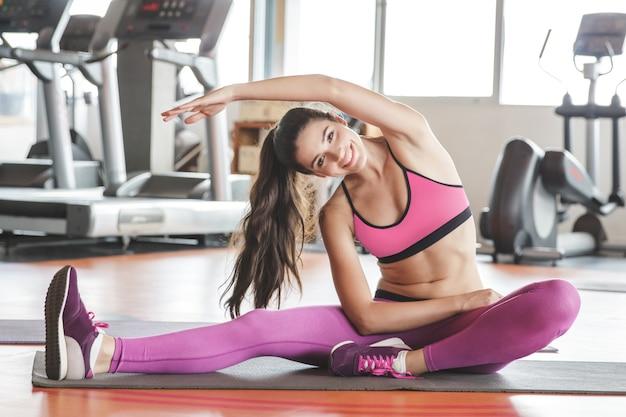 Schöne sportliche frau, die yoga körperdehnung im fitnessstudio tut