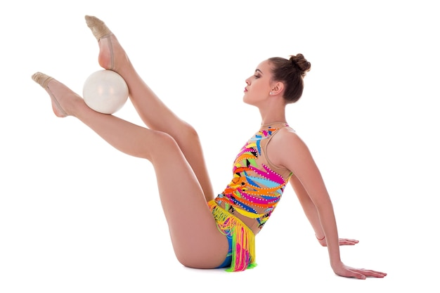 Schöne sportliche frau im bunten body beim turnen mit ball isoliert auf weißem hintergrund
