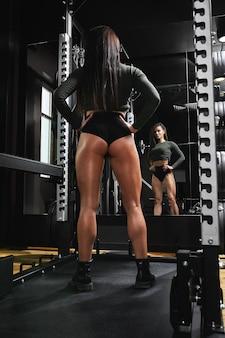 Schöne sportliche frau macht kniebeugen im fitnessstudio