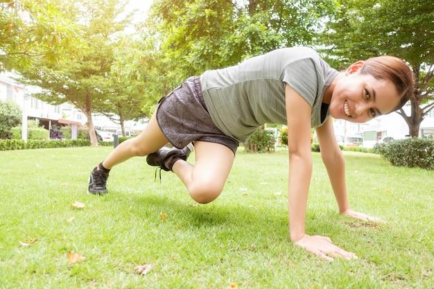 Schöne sportliche frau macht übungen im grünen park