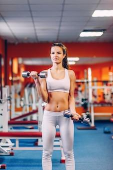 Schöne sportliche frau mit perfektem körper, der workouts mit hanteln für bizeps im fitnessstudio tut