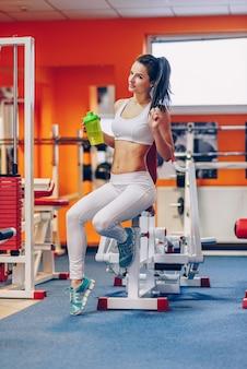 Schöne sportliche frau mit perfektem körper hält die shaker-flasche im fitnessstudio in der hand