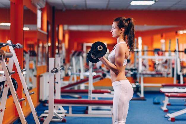 Schöne sportliche frau mit perfektem körpertraining bizeps in der turnhalle