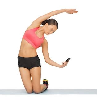 Schöne sportliche frau mit smartphone beim sport