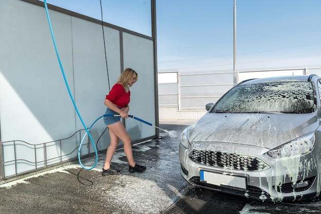 Schöne sportliche frau wäscht auto mit schaum bei autowäsche