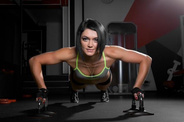 Schöne sportliche frau wird im fitnessstudio hochgeschoben