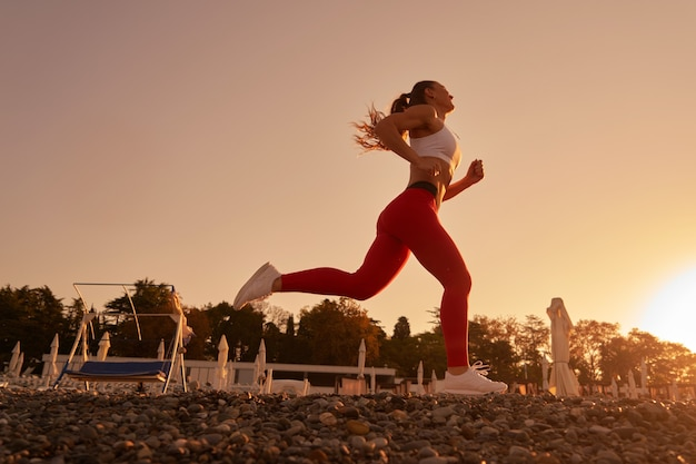 Schöne sportliche frauschattenbild in der sportkleidung, die im morgengrauen joggt