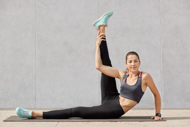 Schöne sportliche junge frau in der stilvollen sportbekleidung, die drinnen gegen graue wand trainiert, frau sitzt auf boden, macht dehnübungen nach hartem training, hält fit.
