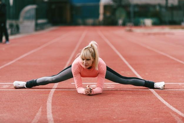 Schöne sportliche kaukasische blonde frau in der sportbekleidung, die sich auf der rennstrecke ausbreitet.