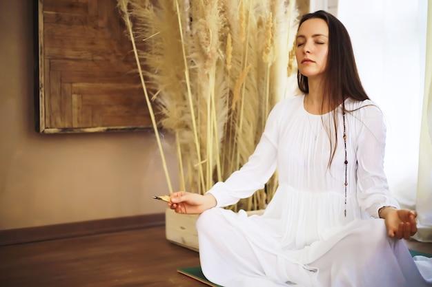 Schöne sportliche mädchen, die yoga-übungen machen, genießen meditation zu hause. kein stress, gesunde gewohnheit, konzept zur linderung von angstzuständen. lotus-pose.