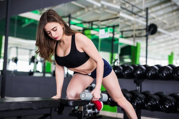 Schöne sportliche muskulöse frau, die mit zwei hanteln ausarbeitet