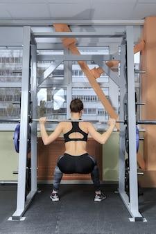 Schöne sportliche sexy frau beim kniebeugentraining im fitnessstudio
