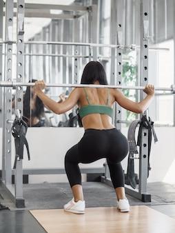Schöne sportliche sexy frau, die kniebeugen-training im fitnessstudio macht