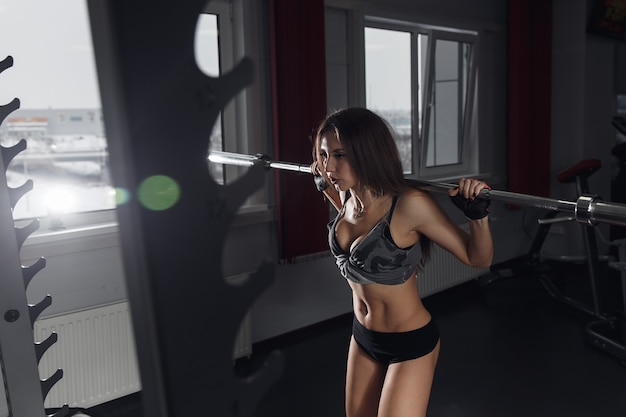 Schöne sportliche sexy frau, die kniebeugentraining in der turnhalle tut.