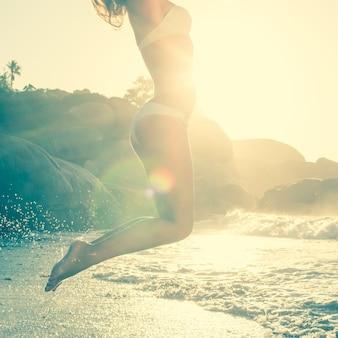 Schöne springende blondine im weißen bikini am strand