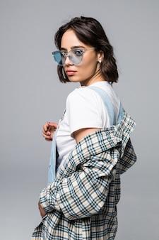 Schöne städtische frau, die trendige sonnenbrille und pullover über schultern trägt und für werbung oder verkaufsförderung aufwirft