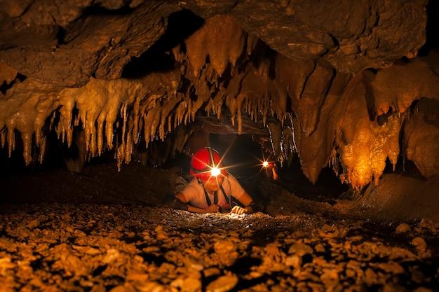 Schöne stalaktiten in einer höhle, schmale höhlenpassage mit einem höhlenforscher underground, thailand