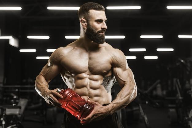 Schöne starke athletische muskeln männer trinken wasser und sporternährungstraining bodybuilding-konzept