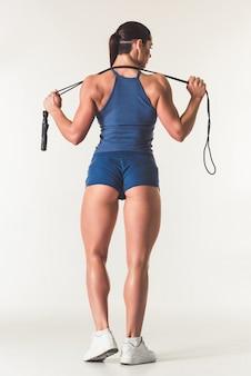 Schöne starke frau in der sportkleidung, die springseil hält.
