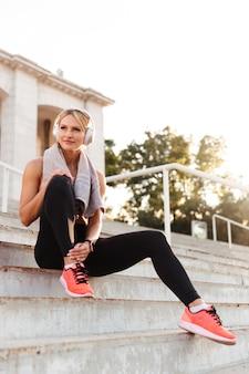 Schöne starke junge sportfrau, die auf stufen sitzt