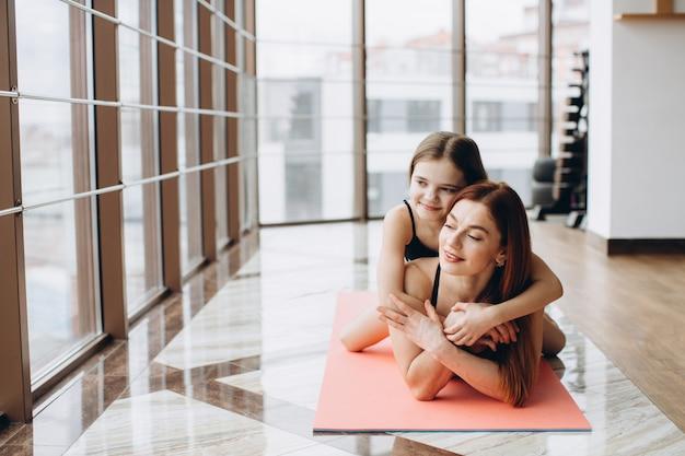 Schöne starke und muskulöse frau und charmantes kleines mädchen liegen auf yogamatte in der fitnesshalle