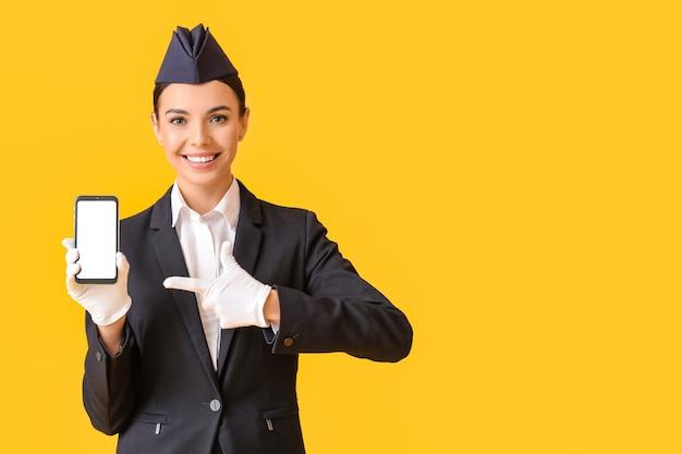 Schöne stewardess mit handy auf farbe