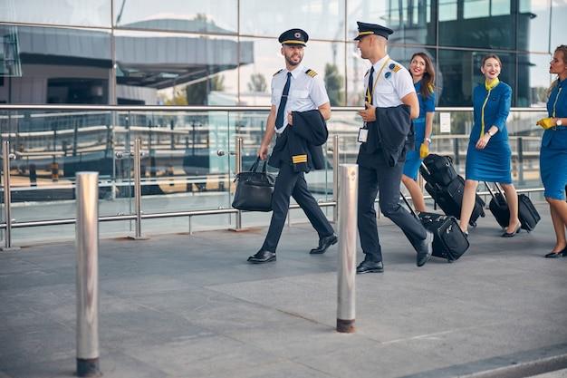 Schöne stewardessen und gutaussehende piloten, die sich unterhalten und lächeln, während sie trolleys am flughafen tragen