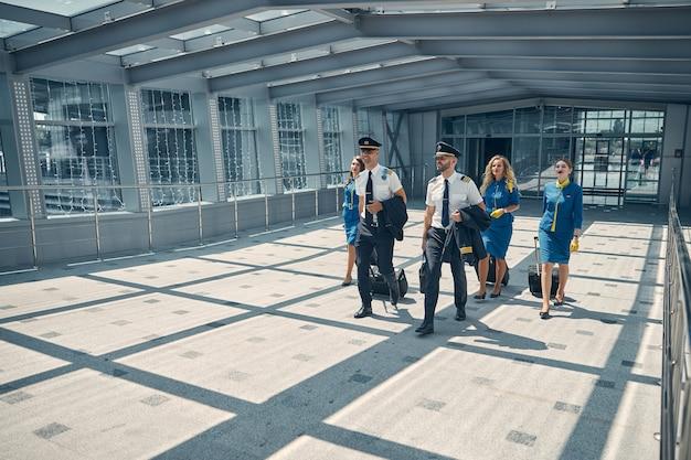 Schöne stewardessen und gutaussehende piloten, die trolleys tragen und lächeln, während sie durch das flughafenterminal schlendern