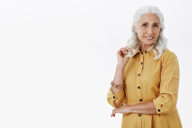 Schöne stilvolle alte dame, die über weißem hintergrund lächelt